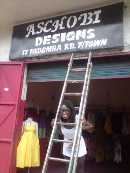 The designer Adama poses by her store in Freetown