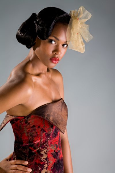 Sumptous ruby couture dress accessorized with a vintage inspired hair-piece