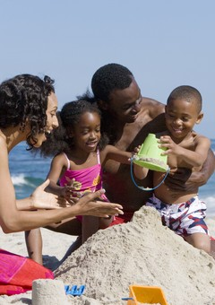 African American family making sand castle together on beach