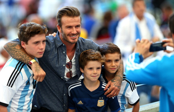 Former England international David Beckham and sons Brooklyn Beckham (L), Cruz Beckham (2nd R) and Romeo Beckham (R)