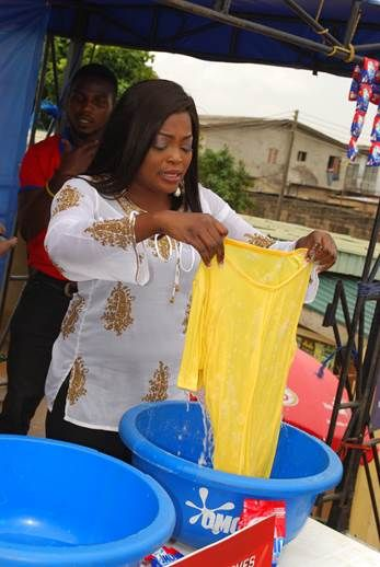 Funke Akindele demonstrating the fast action power of the New OMO Detergent