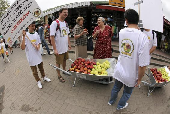 Young people march with a wheel barrow of apples during an event promoting Polish apples in Warsaw