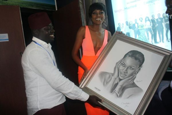 Fan presents a drawing of producer/actress Yvonne Nelson