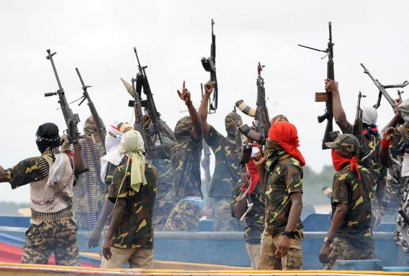 "Fighters with the Movement for the Emancipation of the Niger Delta (MEND) raise their riffles to celebrate news of a successful operation by their colleagues against the Nigerian army in the Niger Delta on September 17, 2008. MEND has declared a full-scale ""oil war"" against the Nigerian authorities in response to attacks by the Nigerian military launched against the militants. ""Our target is to crumble the oil installations in order to force the government to a round table to solve the problem once and for all"", said Boy Loaf, leader of the militants. AFP PHOTO/PIUS UTOMI EKPEI (Photo credit should read PIUS UTOMI EKPEI/AFP/Getty Images)"