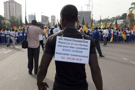 A man wears a sign on his back with his request to be trained and sent to the front line to fight against the Boko Haram attends a march in support of the Cameroonian army in Yaounde
