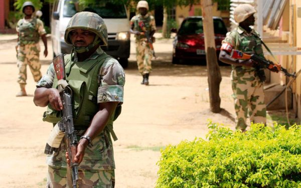 FILE - In this Thursday, June 6, 2013 file photo Nigerian soldiers stand guard at the offices of the state-run Nigerian Television Authority in Maiduguri, Nigeria.