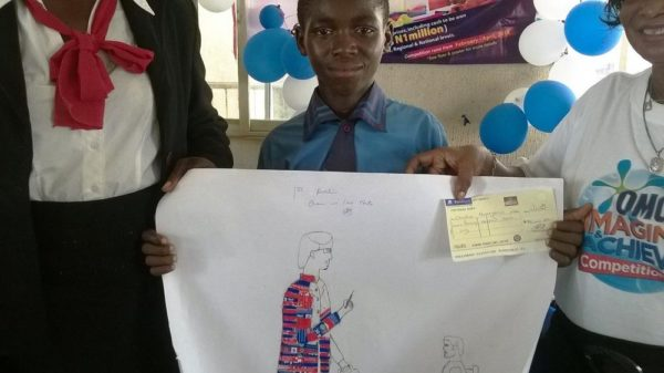 Christian Nwaegaruo, Nomadic Primary School, winner of the first position displaying his cheque of 70 thousand naira in the Imagine and Achieve Art Competition in Imo State
