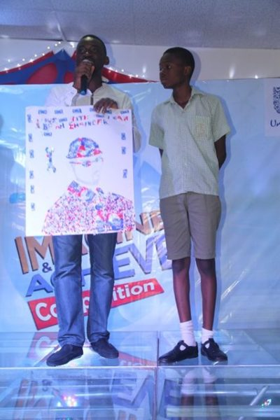 Assistant Category Manager Fab Cleaning, Unilever Nigeria, Adetayo Adesokan and winner of 200 thousand naira, from De Brain Foundation School, Kaduna, Sunday Daniel at the Omo Imagine and Achieve Competition grand finale in Lagos