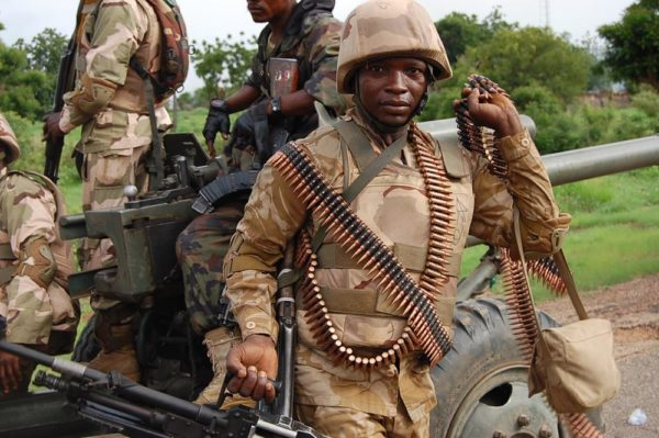 Nigerian troops in a TATA truck enter Damboa with a M56-2 howitzer trailing. Nigerian soldiers clustered around a M56-2 105mm artllery piece at Damboa - source - beegeagle.com