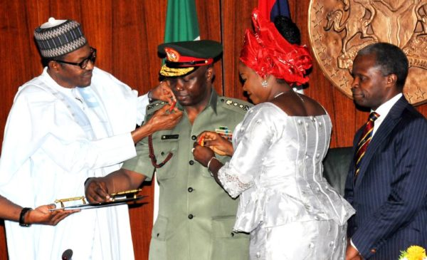 PIC.5.PRESIDENT MUHAMMADU BUHARI (L)  AIDED BY WIFE OF THE CHIEF OF  DEFENCE STAFF, MRS OMOBOLANLE IN DECORATING THE CHIEF OF DEFENCE STAFF,  GEN. ABAYOMI GABRIEL OLONISAKIN,  AT THE PRESIDENTIAL VILLA IN ABUJA ON   THURSDAY (13/8/15) WITH THEM IS  VICE-PRESIDENT YEMI OSINBAJO. 5930/13/8/2015/ICE/CH/NAN