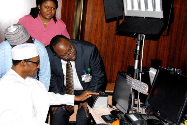 PIC.6. PRESIDENT MUHAMMADU BUHARI BEING CAPTURED FOR THE NATIONAL  IDENTITY MANAGEMENT COMMISSION'S (NIMC) IDENTITY CARD AT THE PRESIDENTIAL  VILLA IN ABUJA ON TUESDAY (25/8/15) WITH HIM IS THE DIRECTOR-GENERAL OF  NIMC, MR CHRIS ONYEMENEM. 6164/25/8/2015/ICE/CH/NAN
