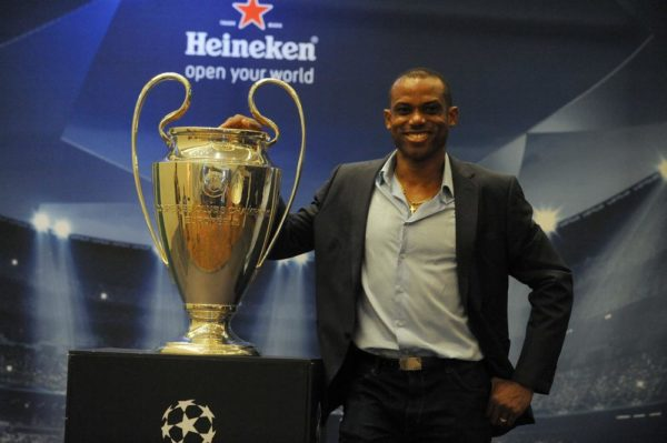 LAGOS, NIGERIA - MARCH 15: Former Nigerian international Sunday Oliseh poses with UEFA Trophy displayed for public viewing at Eko Hotel on March 15, 2014 in Lagos, Nigeria.  Football fans were given the opportunity to visit with the Heineken UEFA Champions League Trophy which began a three-nation tour in Nigeria under the auspices of Champions League partner, Heineken. Fans took photographs with the brand ambassador, former Real Madrid and ex-international football star Christian Karembeu. (Photo by Pius Utomi Ekpei/Getty Images)