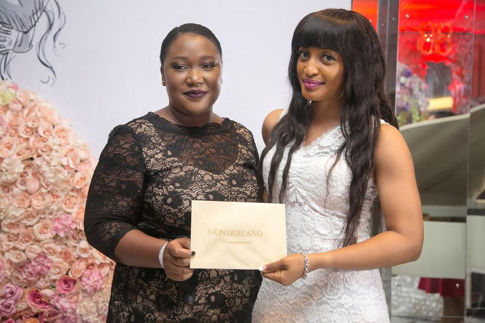 #BBNWonderland bride Lizzy getting the golden envelope for a Honeymoon from AfricHolidays boss Ayomide Condotti