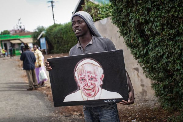 NAIROBI, KENYA - NOVEMBER 24: Artist Simon Kizito tries to sell his painting of Pope Francis in Nairobi's Kangemi slum on November 24, 2015 in Kenya. Pope Francis makes his first visit to Kenya on a five day African tour that is scheduled to include Uganda and the Central African Republic. Africa is recognised as being crucial to the future of the Catholic Church with the continentís Catholic numbers growing faster than anywhere else in the world. (Photo by Nichole Sobecki/Getty Images)
