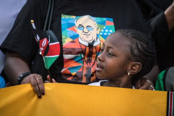 NAIROBI, KENYA - NOVEMBER 25: A young girl waits on the roadside for Pope Francis' convoy to drive through the capital from the airport on November 25, 2015 in Nairobi, Kenya. Pope Francis makes his first visit to Kenya on a five day African tour that is scheduled to include Uganda and the Central African Republic. Africa is recognised as being crucial to the future of the Catholic Church with the continent's Catholic numbers growing faster than anywhere else in the world. (Photo by Nichole Sobecki/Getty Images)