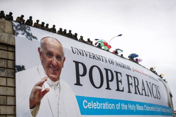 NAIROBI, KENYA - NOVEMBER 26: Security gathers on an overpass above the University of Nairobi grounds on November 26, 2015, to watch a mass delivered by Pope Francis in Nairobi, Kenya. Pope Francis makes his first visit to Kenya on a five day African tour that is scheduled to include Uganda and the Central African Republic. Africa is recognised as being crucial to the future of the Catholic Church with the continent's Catholic numbers growing faster than anywhere else in the world. (Photo by Nichole Sobecki/Getty Images)