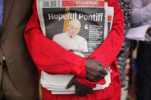 NAIROBI, KENYA - NOVEMBER 26: A man holds a stack of newspapers highlighting Pope Francis' visit to Kenya during a mass at the University of Nairobi grounds on November 26, 2015, in Nairobi, Kenya. Pope Francis makes his first visit to Kenya on a five day African tour that is scheduled to include Uganda and the Central African Republic. Africa is recognised as being crucial to the future of the Catholic Church with the continent's Catholic numbers growing faster than anywhere else in the world. (Photo by Nichole Sobecki/Getty Images)
