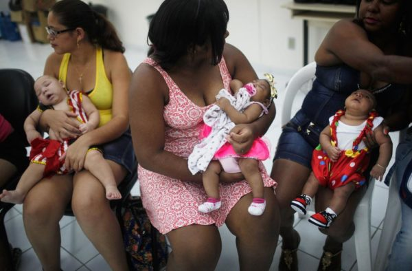 Babies dressed in Carnival outfits, born with microcephaly, are held by their mothers at a Carnival party held for babies with the condition in a health clinic on February 4, 2016 in Recife, Pernambuco state, Brazil. The mosquito-borne Zika virus may have led to microcephaly in infants in Brazil.  (Photo by Mario Tama/Getty Images)