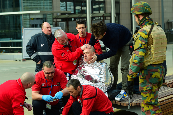A victim receives first aid by rescuers, on March 22, 2016 near Maalbeek metro station in Brussels, after a blast at this station near the EU institutions caused deaths and injuries. AFP PHOTO / EMMANUEL DUNAND / AFP / EMMANUEL DUNAND (Photo credit should read EMMANUEL DUNAND/AFP/Getty Images)