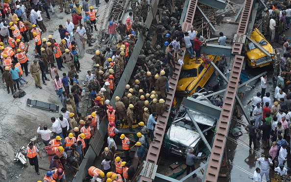 Indian rescue workers and volunteers try to free people trapped under the wreckage of a collapsed fly-over bridge in Kolkata on March 31, 2016. At least 14 people were killed and dozens more injured when a flyover collapsed in a busy Indian city on March 31, an official said, as emergency workers battled to rescue people trapped under the rubble.  / AFP / Dibyangshu SARKAR        (Photo credit should read DIBYANGSHU SARKAR/AFP/Getty Images)