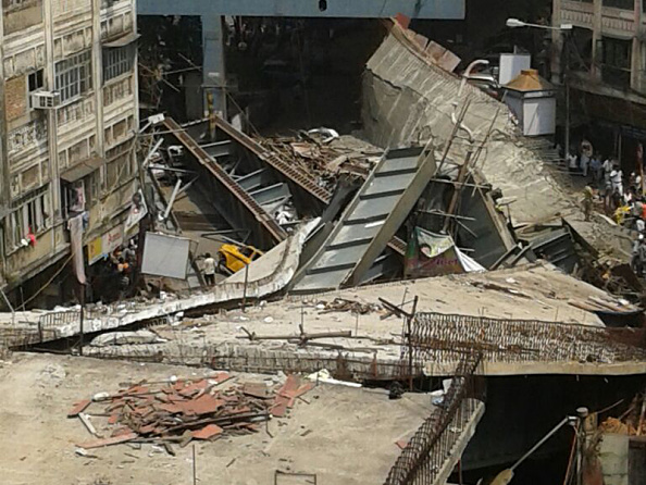KOLKATA, INDIA - MARCH 31: (EDITORS NOTE: Image was created with a smartphone) A part of flyover collapsed on March 30, 2016 in Kolkata, India. At least two people were killed in Kolkata on Thursday and hundreds were feared trapped when an under-construction flyover collapsed onto traffic moving along the street below, police said. Fire-fighters and residents were trying to rescue those trapped under the wreckage of the metal-and-cement structure that came down near Girish Park in a teeming commercial district. (Photo by Hindustan Times)