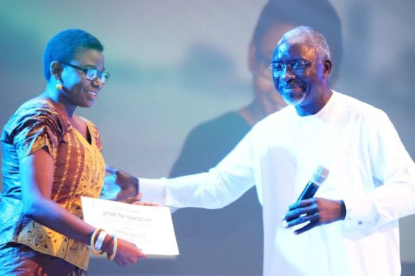 Patron of the Etisalat Prize for Literature, Dele Olojede presenting the prize to the winner of the 2014 Etisalat Prize for Literature Flash Fiction Category, Neema Komba