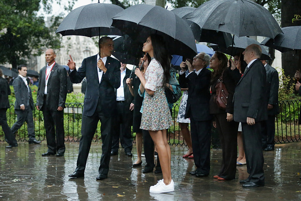 HAVANA, CUBA - MARCH 20:  Taking shelter from the pouring rain under umbrellas, U.S. President Barack Obama, his daughter Malia, 17, and members of the first family take a walking tour of in the plaza of the 18th century Catedral de San Cristobal de la Habana in the historic Old Havana neighborhood March 20, 2016 in Havana, Cuba. Obama is the first sitting president to visit Cuba in nearly 90 years.  (Photo by Chip Somodevilla/Getty Images)