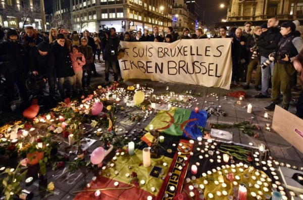 "People holding a banner reading ""I am Brussels"" behind flowers and candles to mourn for the victims at Place de la Bourse in the center of Brussels, Tuesday, March 22, 2016. Bombs exploded at the Brussels airport and one of the city's metro stations Tuesday, killing and wounding scores of people, as a European capital was again locked down amid heightened security threats. (AP Photo/Martin Meissner)"