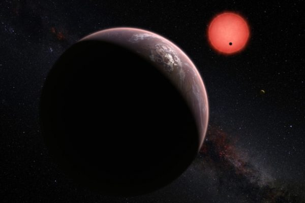 This artist's rendering shows an imagined view of the three planets orbiting an ultracool dwarf star just 40 light-years from Earth that were discovered using the TRAPPIST telescope at ESO's La Silla Observatory. In this view, one of the inner planets is seen in transit across the disc of its tiny and dim parent star. Image: M. Kornmesser/ESO via MIT News