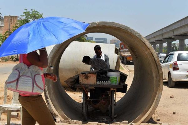 An Indian roadside food vendor sets up his cart inside a concrete pipe in Gurgaon on the outskirts of New Delhi on May 27, 2015. IMAGE: CHANDAN KHANNA/AFP/GETTY IMAGES