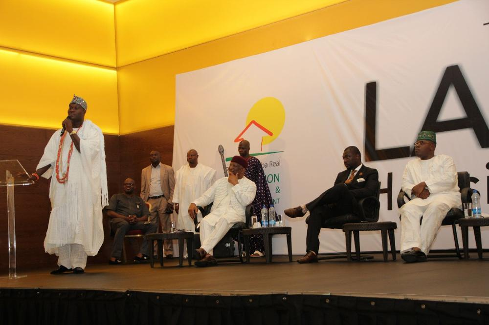 Ooni Of Ife making a speech at the event. Others on Stage are Hon. Gbolahan Lawal, Honorable Commissioner for Housing, Lagos State, (representing Governor Ambode) Dr. Newton Jibunor, Chairman, Roland Igbinoba Real Foundation for Housing and Urban Development (RIRFHUD) and Mr. Roland Igbinoba, Executive Vice Chairman, Roland Igbinoba Real Foundation for Housing and Urban Development (RIRFHUD)