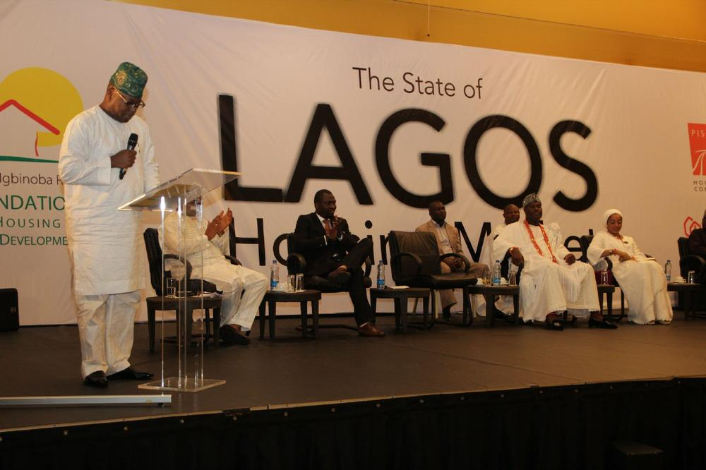 Hon. Gbolahan Lawal, Honorable Commissioner for Housing, Lagos State, (representing Governor Ambode) making a speech. Others on stage are Ooni of Ife and His Wife, Dr. Newton Jibunor, Chairman,(RIRFHUD) and Mr. Roland Igbinoba, Executive Vice Chairman, (RIRFHUD)