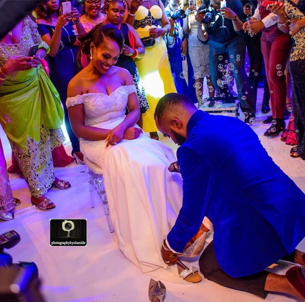 He has the sweet touch! Noble Igwe changing his Bride's Shoes at Their Wedding | Photo Credit: Photography by Olumide