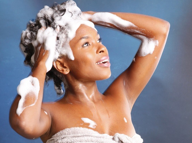 Black-woman-shampooing-her-hair stock photo