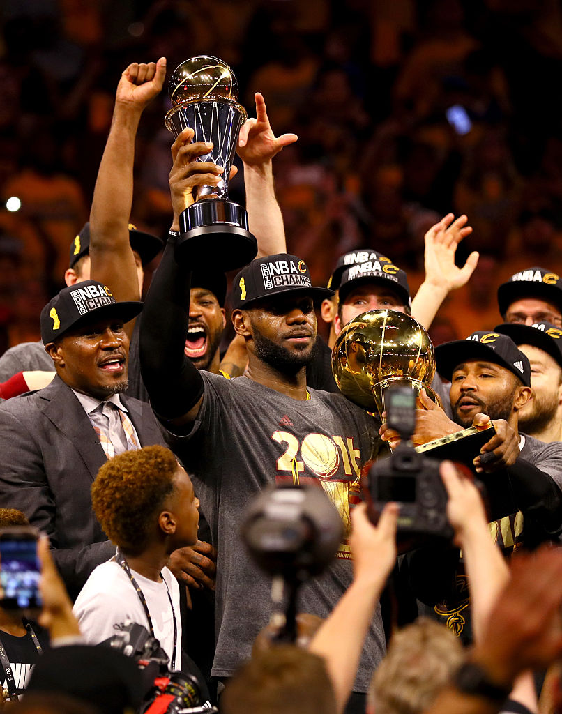 OAKLAND, CA - JUNE 19: LeBron James #23 of the Cleveland Cavaliers holds the Larry O'Brien Championship Trophy and the Bill Russell NBA Finals Most Valuable Player Award after defeating the Golden State Warriors 93-89 in Game 7 of the 2016 NBA Finals at ORACLE Arena on June 19, 2016 in Oakland, California. (Photo by Ezra Shaw/Getty Images)