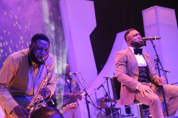 Mike Aremu and Praiz performing on stage