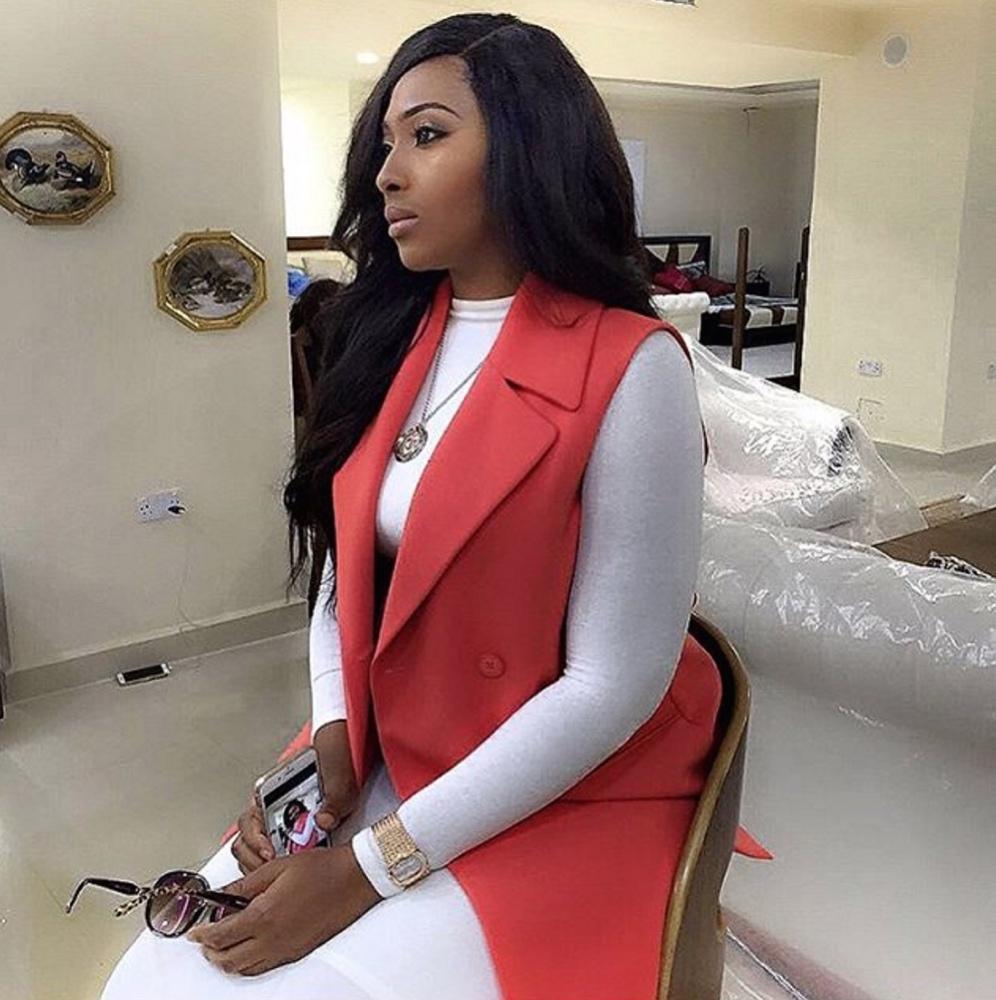 Lilian Esoro wears a long, sleeveless jacket for a pop of colour on a white dress