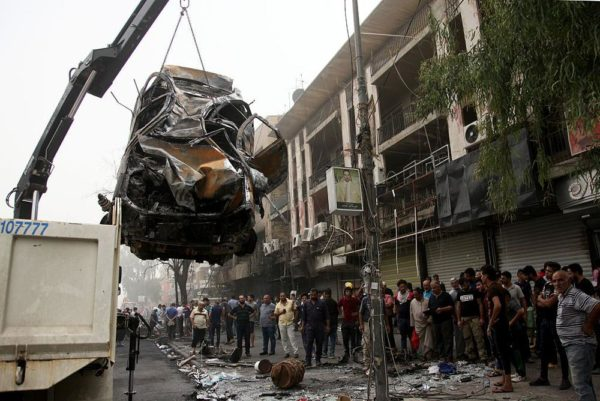 BAGHDAD, IRAQ - JULY 03: Damaged car is lifted after a suicide car bombing, claimed by the terrorist organization DAESH, in the Karrada neighborhood of Baghdad, Iraq on July 03, 2016. It is reported that 60 people were killed and 100 wounded in the blast. (Photo by Amir Saadi/Anadolu Agency/Getty Images)