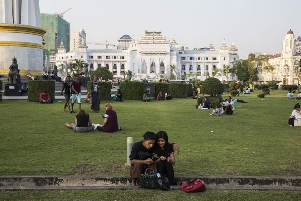 A couple look at a mobile device while other visitors and tourists sit in Maha Bandoola Garden as Yangon City Hall stands in the background, in Yangon, Myanmar, on Thursday, Feb. 4, 2016. Aung San Suu Kyi's party assumed control of the nation's parliament earlier this month as more than half a century of military rule in the country comes to an end. Photographer: Taylor Weidman/Bloomberg via Getty Images