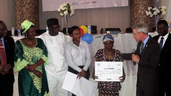 USAID MD Mike Harvey (2nd right) presenting a cash voucher to one of the beneficiaries of a cash transfer program to assist HIVAIDS affected children and families in Edo State. (1) - Copy