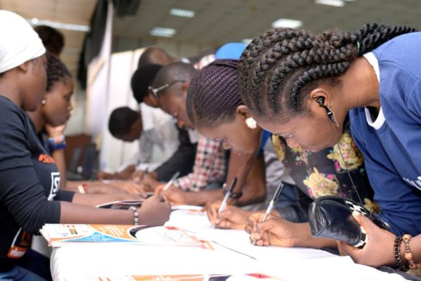 Participants registering by the registration stand at the #IYD2016NG event