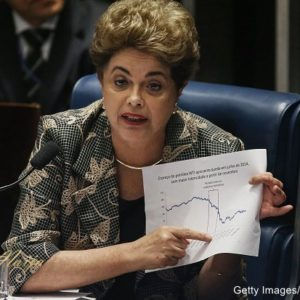 President Dilma Rousseff points to an economic chart displaying oil prices while answering a question from a Senator on the Senate floor during her impeachment trial on August 29, 2016 in Brasilia, Brasil. Senators will vote in the coming days whether to impeach and permanently remove Rousseff from office. (Photo by Mario Tama/Getty Images)