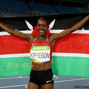 RIO DE JANEIRO, BRAZIL - AUGUST 16: Faith Chepngetich Kipyegon of Kenya celebrates with the flag of Kenya after winning the gold medal in the Women's 1500m Final on Day 11 of the Rio 2016 Olympic Games at the Olympic Stadium on August 16, 2016 in Rio de Janeiro, Brazil. (Photo by Ian Walton/Getty Images)