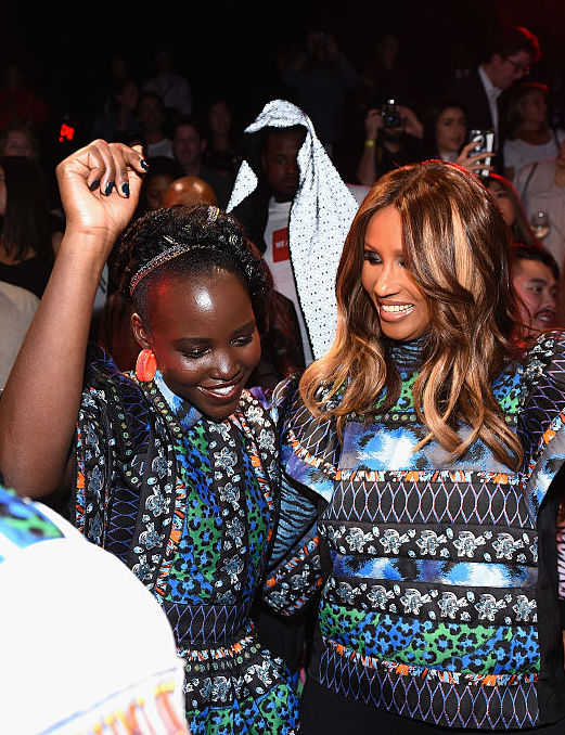 NEW YORK, NY - OCTOBER 19: Lupita Nyong'o, Iman, and Xiuhtezcatl Martinez dance at the KENZO x H&M Launch Event Directed By Jean-Paul Goude' at Pier 36 on October 19, 2016 in New York City. (Photo by Dimitrios Kambouris/Getty Images for H&M)
