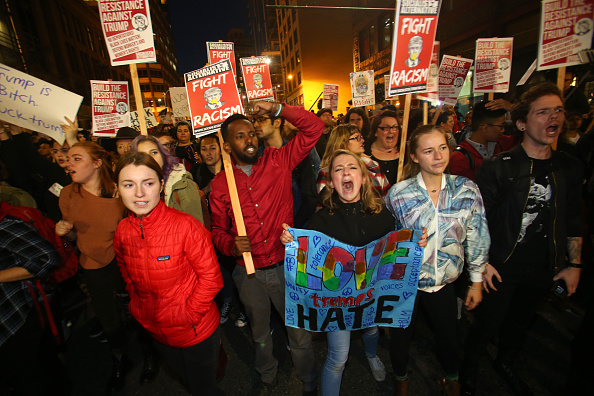 SEATTLE, WA - NOVEMBER 09: (EDITORS NOTE: Image contains profanity) Emma Esselstyn (C) a student from the University of Washington, join thousands of protesters march down 2nd Avenue on November 9, 2016 in Seattle, Washington. Demostrations in multiple cities around the country were held the day following Donald Trump's upset win in last night's U.S. presidential election.  (Photo by Karen Ducey/Getty Images)