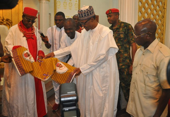 Oba Ewuare II of Benin show President Buhari the wrapper with his inauguration picture