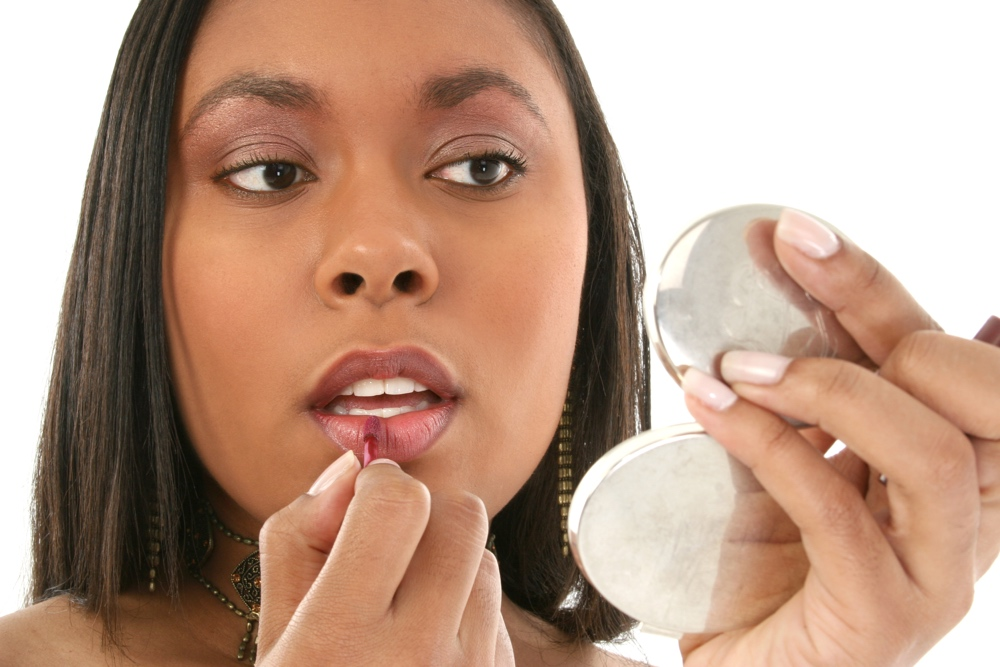 dreamstime_african-american-woman-putting-on-makeup-lipgloss-with-compact-mirror