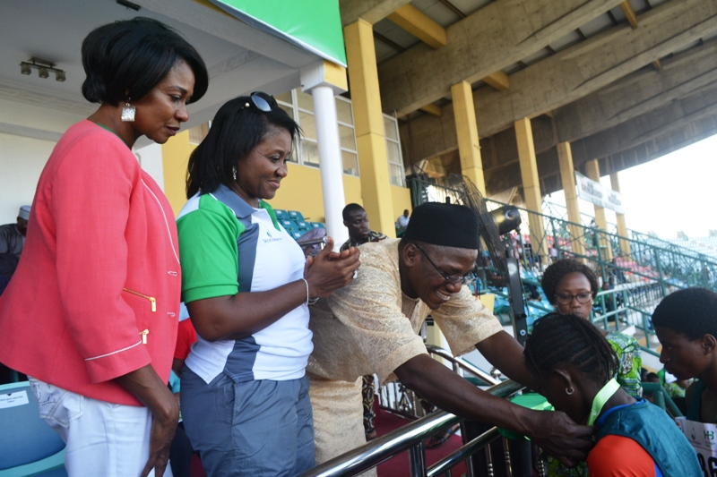 L-R: Heritage Bank-Lagos State Skoolimpics Brand Ambassador, Mary Onyali; Executive Director, Heritage Bank, Mary Akpobome and the Minister of Sports and Youth Development, Mr. Solomon Dalung decorating a winner with a medal at the closing ceremony of the pilot edition of the bank's signature sporting event, Skoolimpics