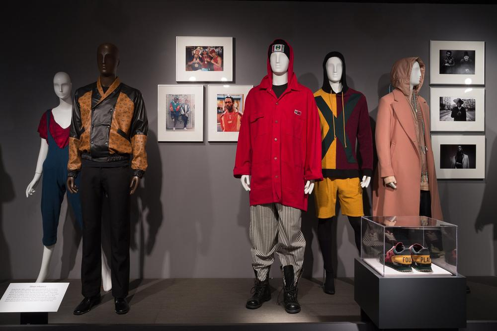 Photo credits (from left to right): Isaïa, ensemble, 1980, USA. Gift of Ms. Terry Melville. Dapper Dan of Harlem, jacket, 1987, USA. Gift of Dapper Dan of Harlem. Photographs by Jamel Shabazz, late-1980s. Cross Colours, ensemble, 1990-1993, USA. Gift of Michael Harrell. Photographs by Dario Calmese 2012-2014. Off-White, ensemble, fall 2015, USA. Gift of Off-White c/o Virgil Abloh. Pyer Moss, ensemble and shoes (in case), fall 2015, USA. Gift of Pyer Moss.