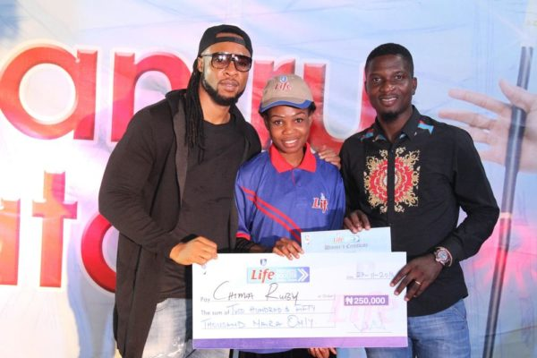 Flavour brand ambassador for Life Continental Beer, and Akinola Josiah Olufemi, Assistant Brand Manager, Regional Mainstream Brands, NB Plc presenting a cheque of N250, 000 to Chima Ruby, one of the winners of the Life Progress Booster Show in Onitsha.
